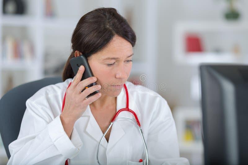 Doctor de sexo femenino joven que habla en el tel?fono m?vil foto de archivo libre de regalías
