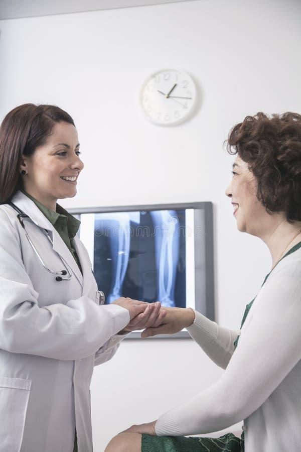 Doctor de sexo femenino joven que lleva a cabo las manos de un paciente fotografía de archivo