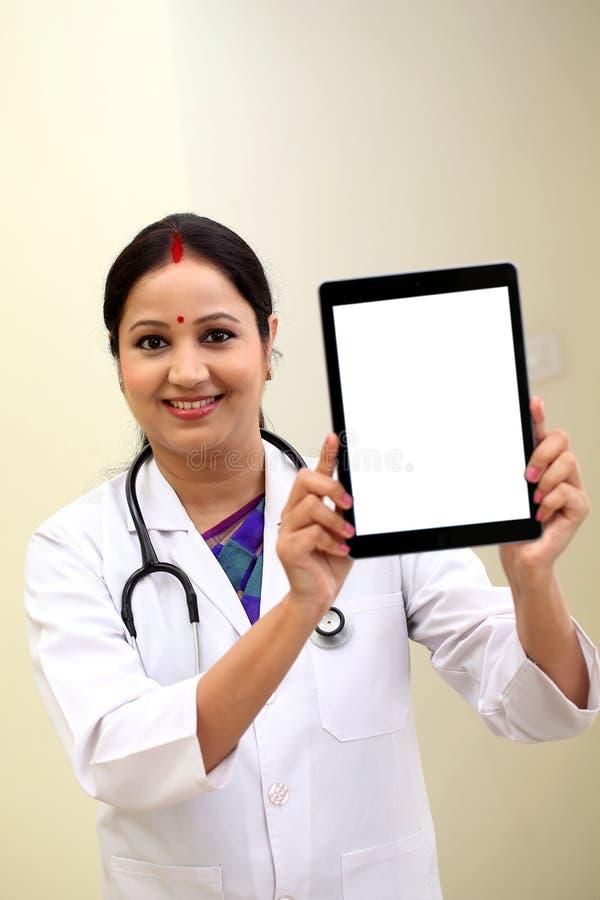 Doctor de sexo femenino joven que muestra la tableta blanca en blanco de la pantalla foto de archivo libre de regalías