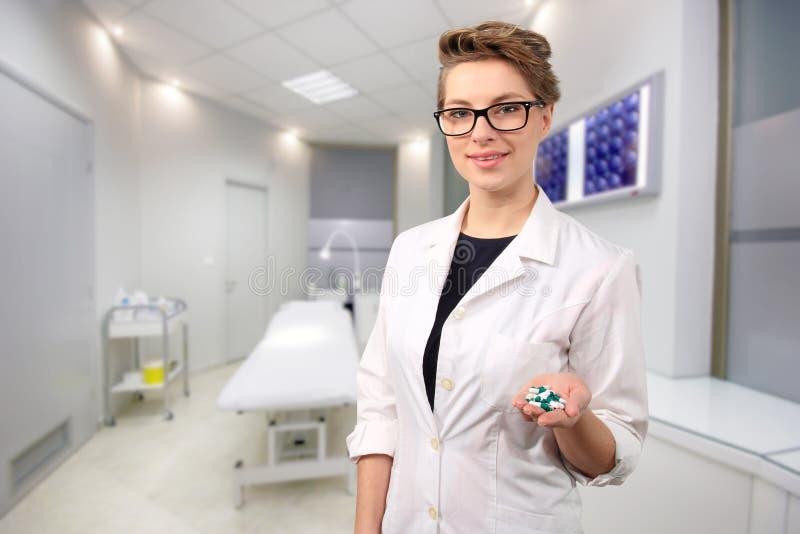 Doctor de sexo femenino joven que sostiene píldoras fotografía de archivo