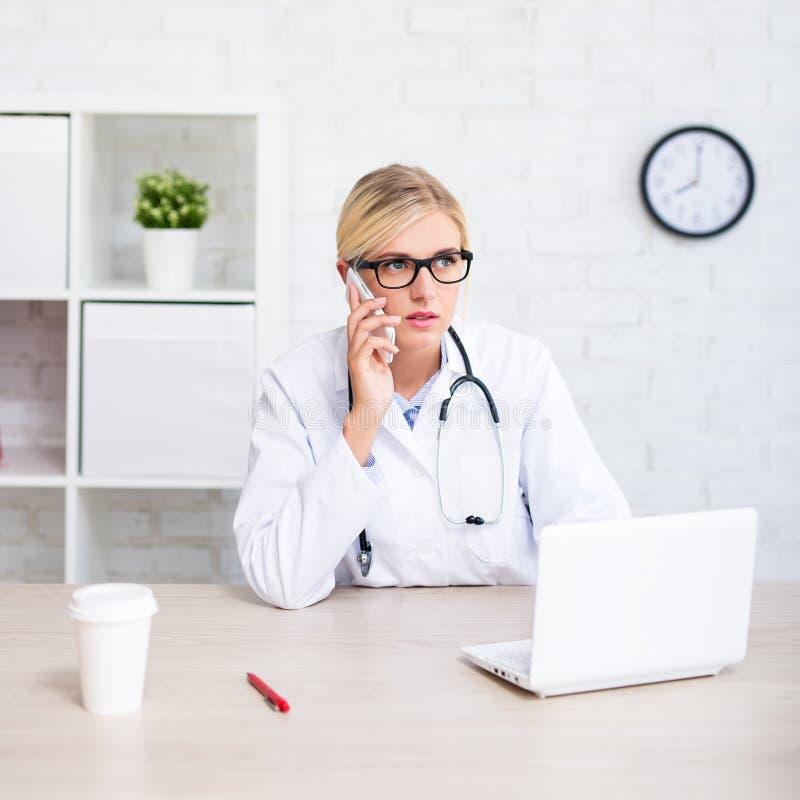 Doctor de sexo femenino joven que trabaja con el ordenador y que habla por el teléfono i fotos de archivo libres de regalías