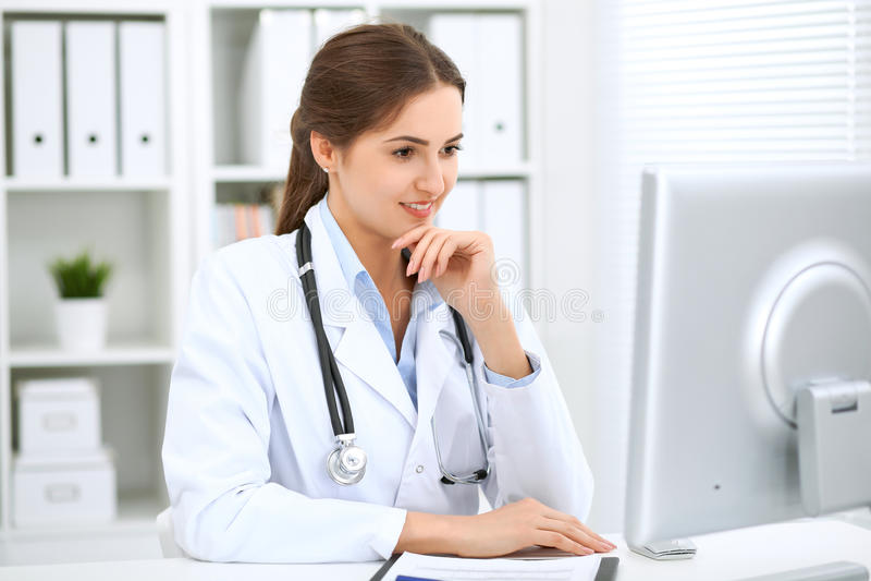 Doctor de sexo femenino latinoamericano que se sienta en la tabla y que trabaja por el ordenador en la oficina del hospital El mé imagen de archivo libre de regalías