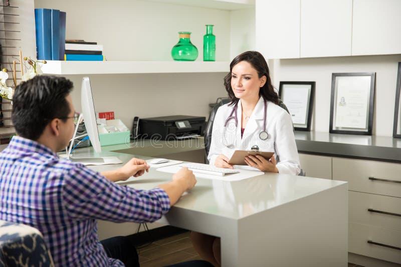Doctor de sexo femenino lindo con un paciente imagenes de archivo