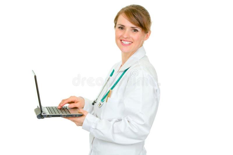 Doctor de sexo femenino médico sonriente que usa la computadora portátil imágenes de archivo libres de regalías