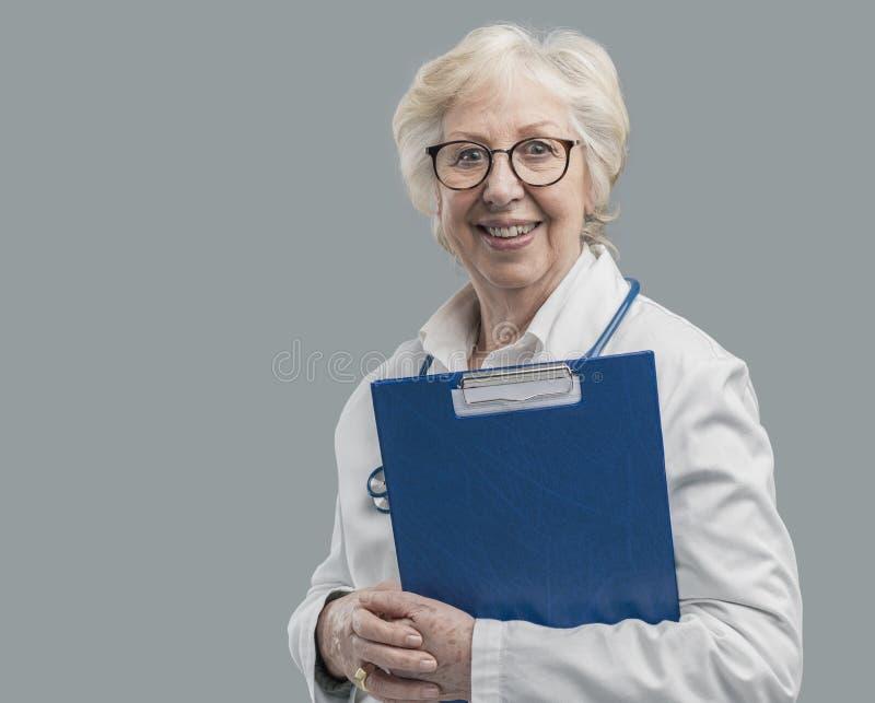 Doctor de sexo femenino mayor confiado que presenta y que sonríe imágenes de archivo libres de regalías