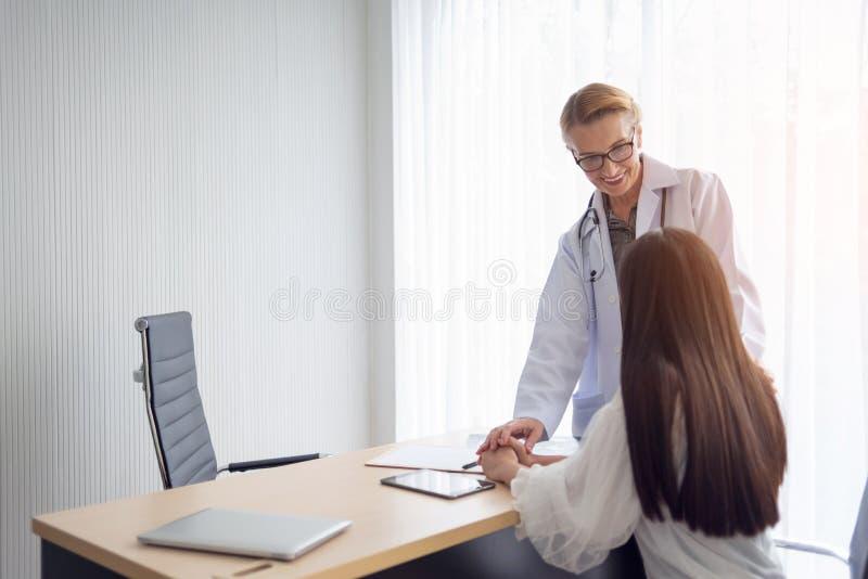 Doctor de sexo femenino mayor sonriente que habla y que tranquiliza a su paciente imagenes de archivo