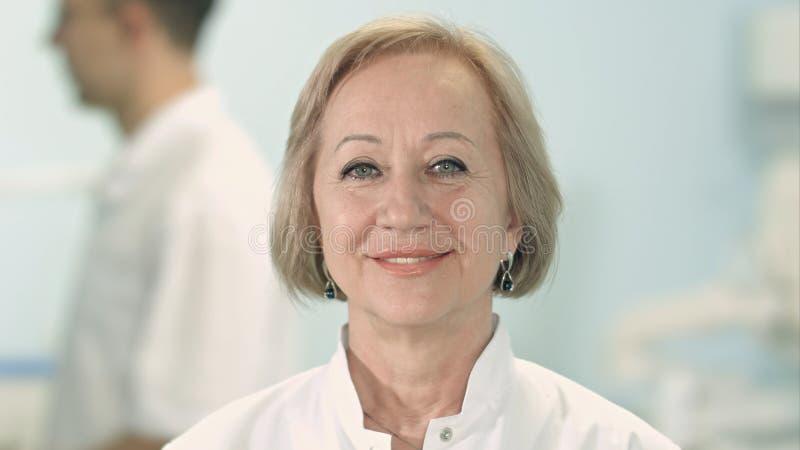 Doctor de sexo femenino mayor sonriente que mira la cámara foto de archivo