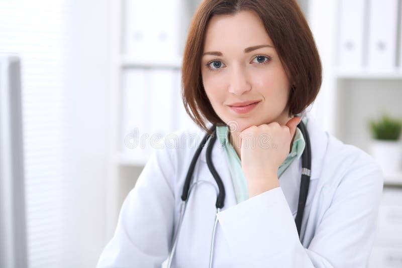 Doctor de sexo femenino moreno joven que se sienta en un escritorio y que trabaja en el ordenador en la oficina del hospital fotografía de archivo