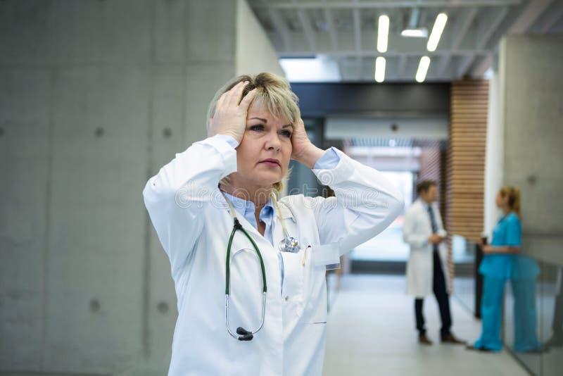 Doctor de sexo femenino pensativo que coloca el pasillo de n imágenes de archivo libres de regalías
