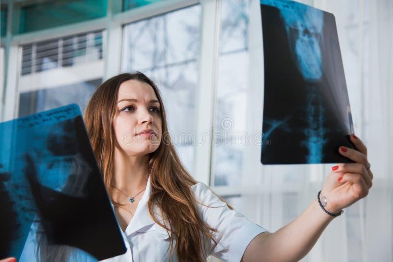 Doctor de sexo femenino profesional joven que examina la radiografía paciente del ` s fotos de archivo libres de regalías