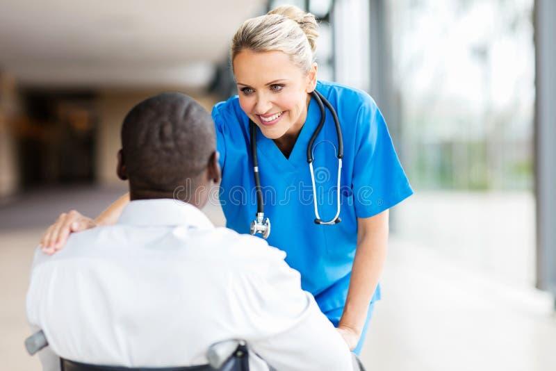 Doctor de sexo femenino que conforta al paciente imagenes de archivo