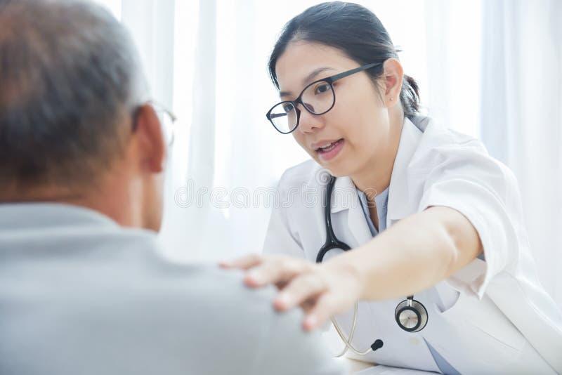 Doctor de sexo femenino que conforta al paciente masculino mayor imagen de archivo libre de regalías