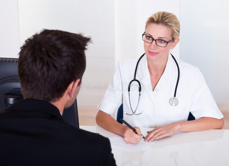 Doctor de sexo femenino que consulta con un paciente foto de archivo libre de regalías