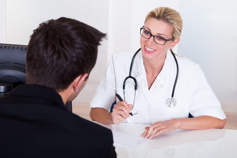 Doctor de sexo femenino que consulta con un paciente imagen de archivo