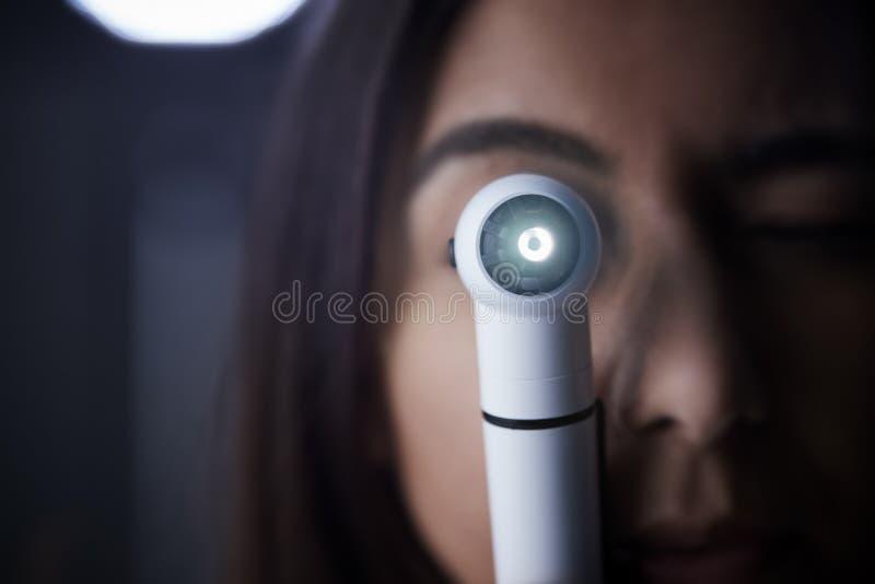 Doctor de sexo femenino que consume el otoscopio para el examen, cierre foto de archivo