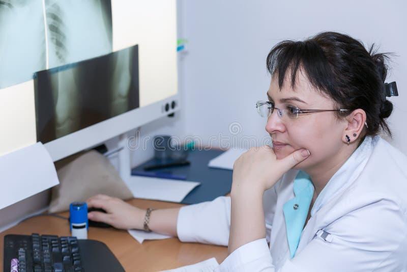 Doctor de sexo femenino que examina una radiografía fotos de archivo