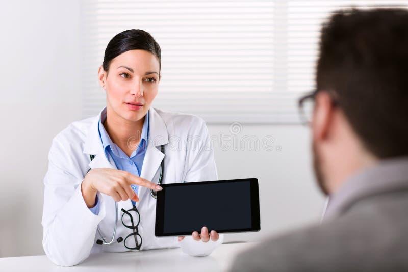 Doctor de sexo femenino que explica algo a un paciente foto de archivo