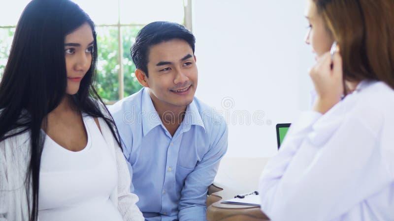 Doctor de sexo femenino que habla con los pares jovenes en sitio del examen fotos de archivo libres de regalías