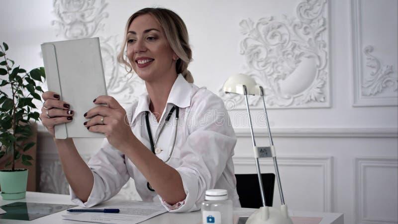 Doctor de sexo femenino que hace el selfie en la tableta en oficina foto de archivo libre de regalías