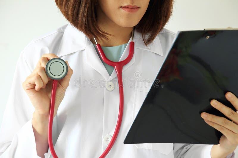 Doctor de sexo femenino que lee una carta paciente del tratamiento imagen de archivo