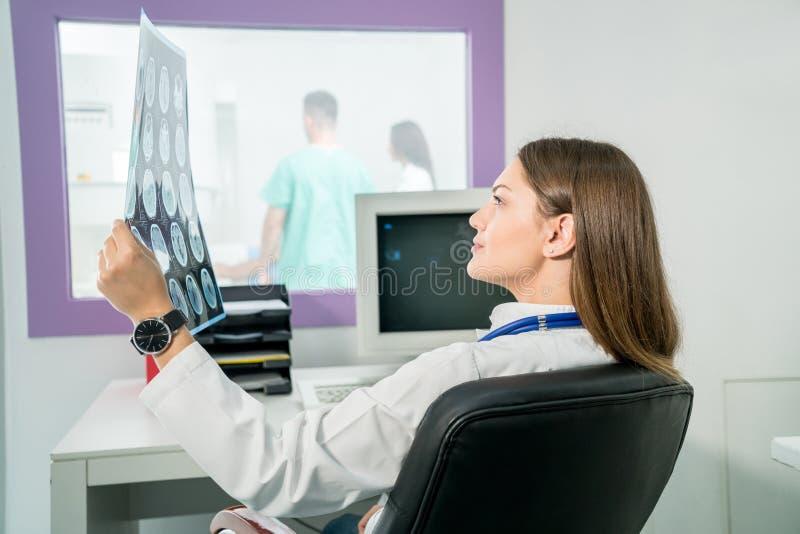 Doctor de sexo femenino que mira una radiografía en su oficina imagenes de archivo