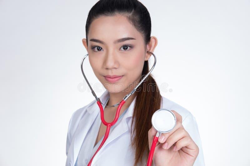 Doctor de sexo femenino que muestra el estetoscopio para el chequeo sobre el backgro blanco imagen de archivo