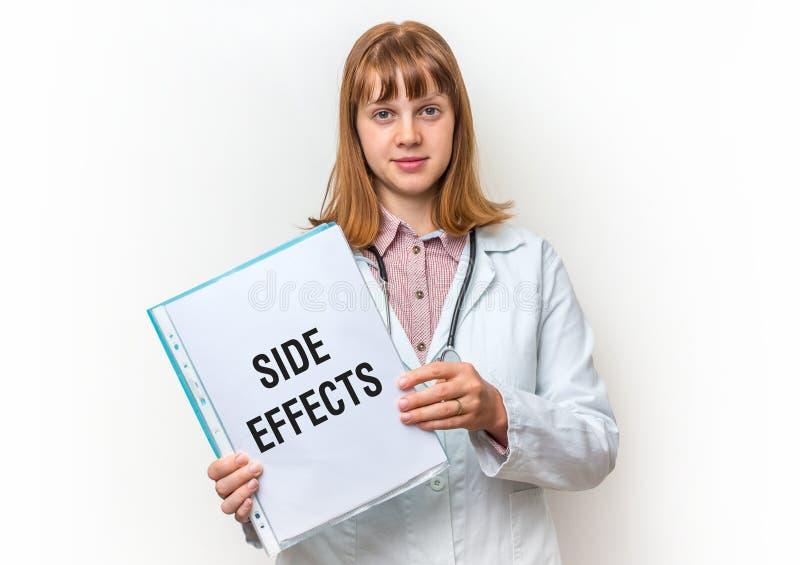 Doctor de sexo femenino que muestra el tablero con el texto escrito: Efectos secundarios fotos de archivo
