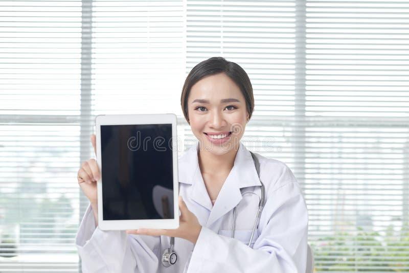 Doctor de sexo femenino que muestra la tableta con la pantalla en blanco al paciente en la oficina imágenes de archivo libres de regalías