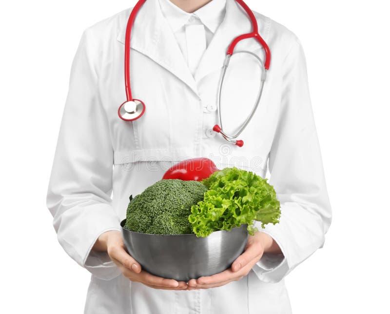 Doctor de sexo femenino que sostiene el cuenco con las verduras sanas en el fondo blanco foto de archivo