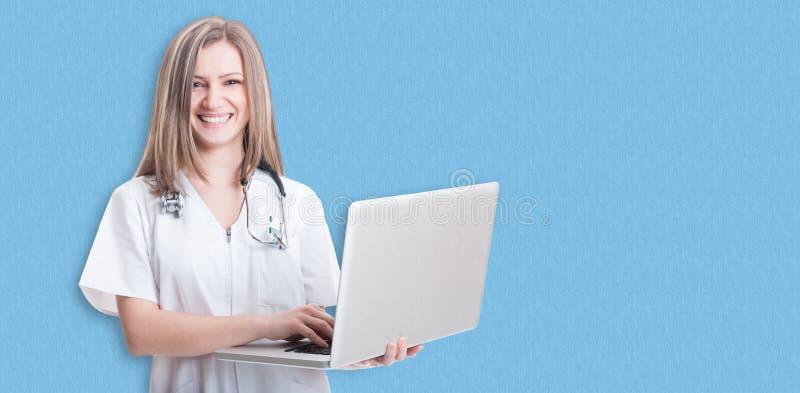 Doctor de sexo femenino que sostiene el ordenador portátil moderno foto de archivo