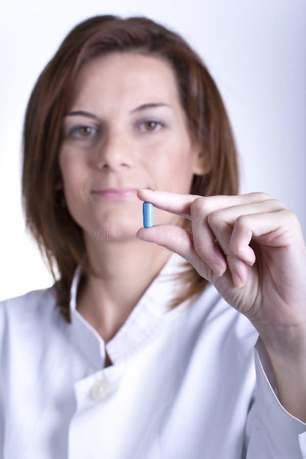Doctor de sexo femenino que sostiene una píldora azul imagen de archivo