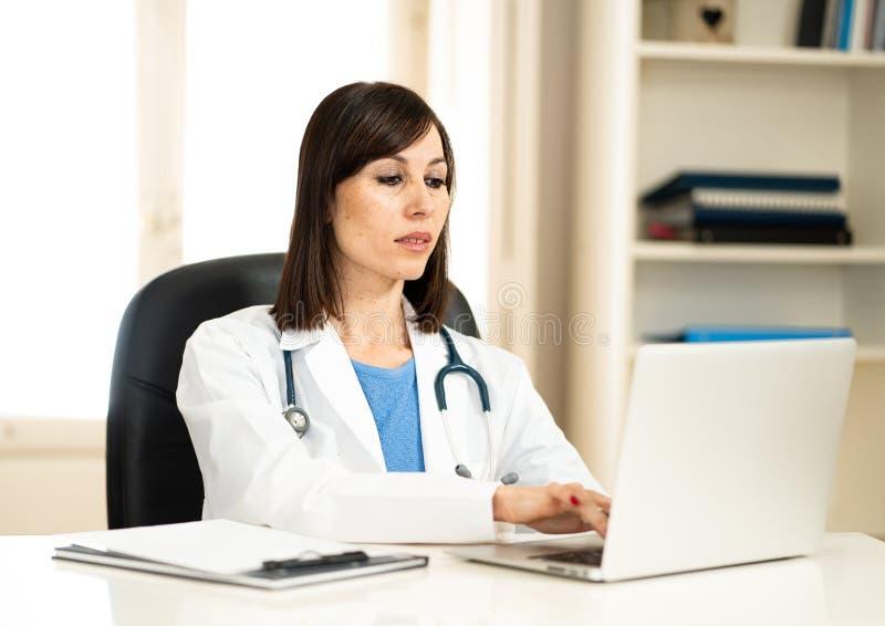 Doctor de sexo femenino que trabaja en experiencia médica y que busca la información sobre el ordenador portátil en la oficina de foto de archivo