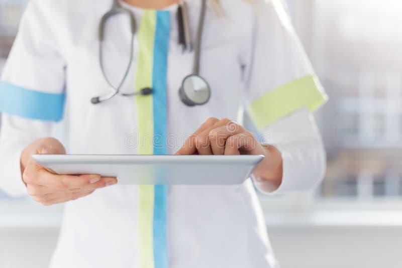 Doctor de sexo femenino que usa el ipad en el trabajo en hospital imagen de archivo