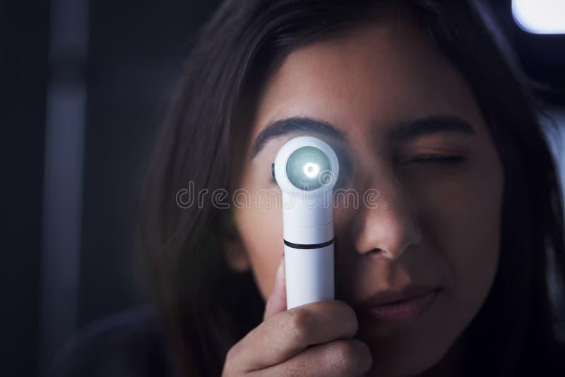 Doctor de sexo femenino que usa el otoscopio para el examen foto de archivo libre de regalías