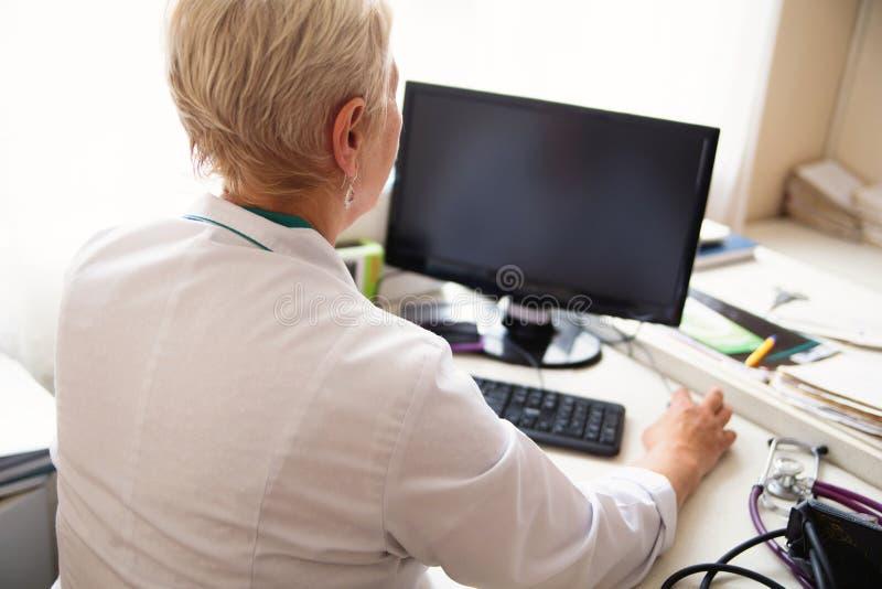 Doctor de sexo femenino que usa PC de sobremesa en clínica foto de archivo