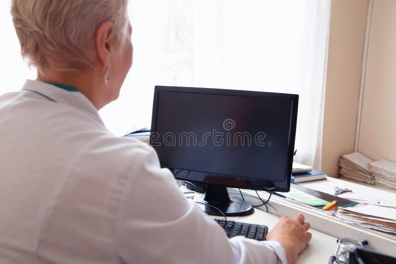Doctor de sexo femenino que usa PC de sobremesa en clínica fotos de archivo libres de regalías