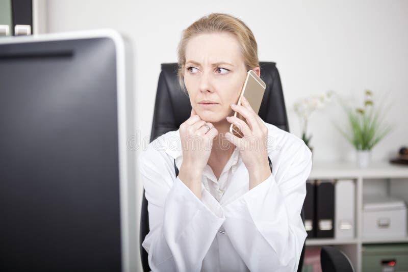 Doctor de sexo femenino serio en el teléfono y mirada a la izquierda foto de archivo