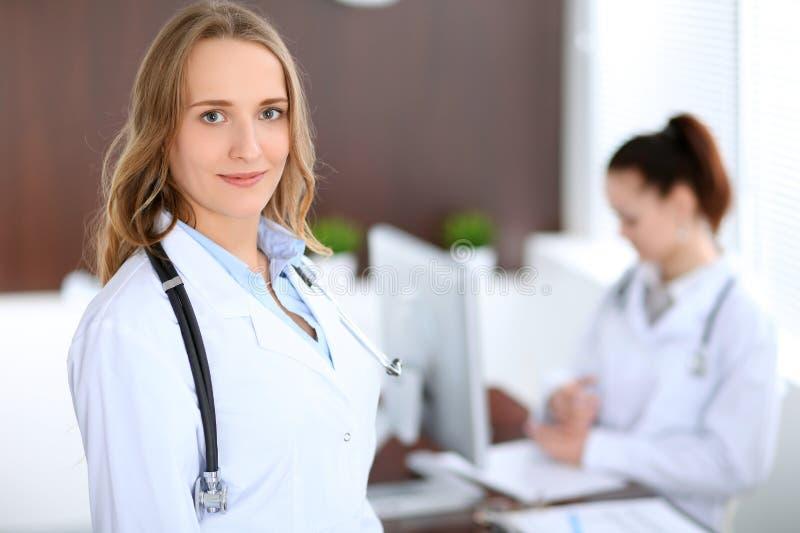 Doctor de sexo femenino sonriente de los jóvenes hermosos que se coloca en un hospital con su colega en el fondo fotografía de archivo
