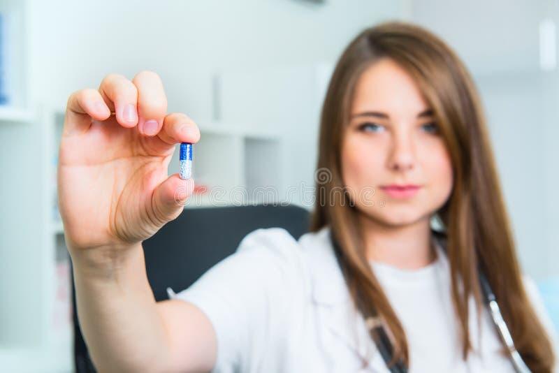 Doctor de sexo femenino sonriente en la capa blanca con el estetoscopio que sostiene una píldora entre sus fingeres La mano de un foto de archivo libre de regalías
