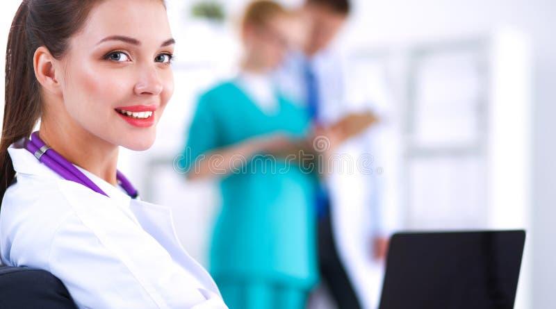 Doctor de sexo femenino sonriente de los jóvenes hermosos que se sienta en el escritorio imagen de archivo