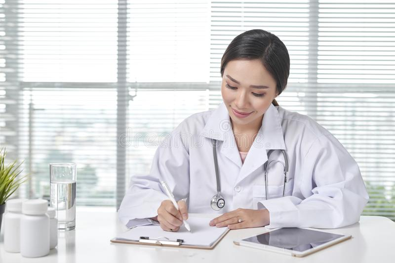 Doctor de sexo femenino sonriente que escribe el documento en el lugar de trabajo en oficina foto de archivo