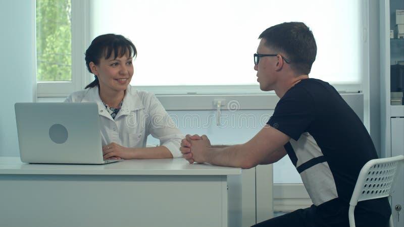 Doctor de sexo femenino sonriente que escucha el paciente masculino en su oficina imagenes de archivo