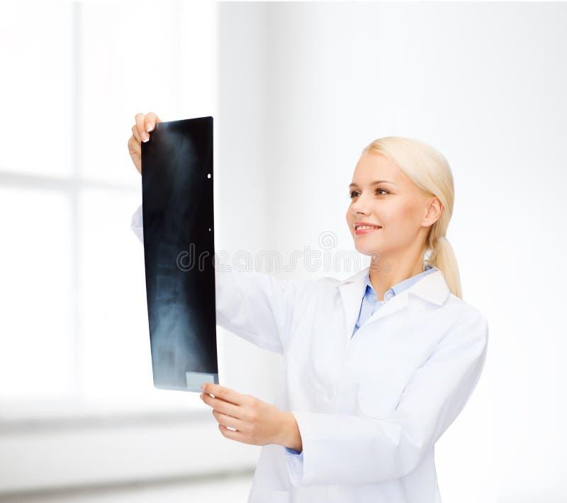 Doctor de sexo femenino sonriente que mira la radiografía imagenes de archivo