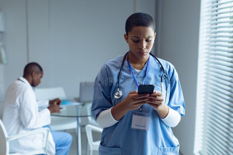 Doctor de sexo femenino usando el teléfono móvil en hospital foto de archivo