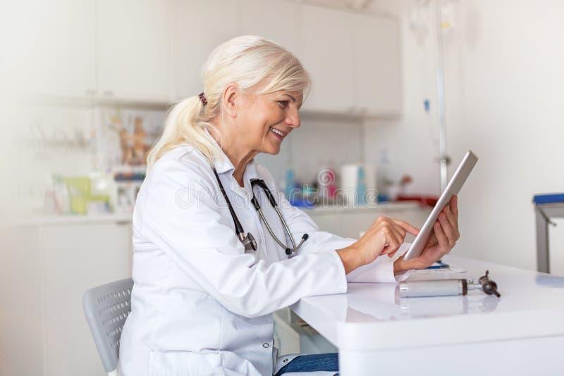 Doctor de sexo femenino usando la tableta digital en su oficina fotos de archivo