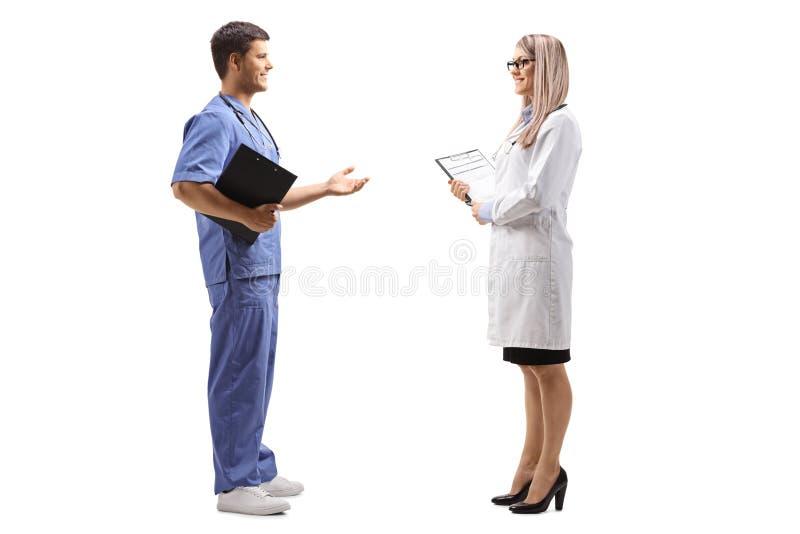 Doctor de sexo femenino y de sexo masculino que tiene una conversación fotografía de archivo