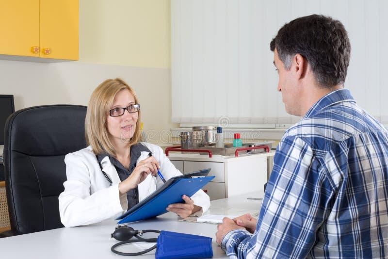 Doctor de sexo femenino y paciente envejecido centro que hablan en sitio de consulta imágenes de archivo libres de regalías
