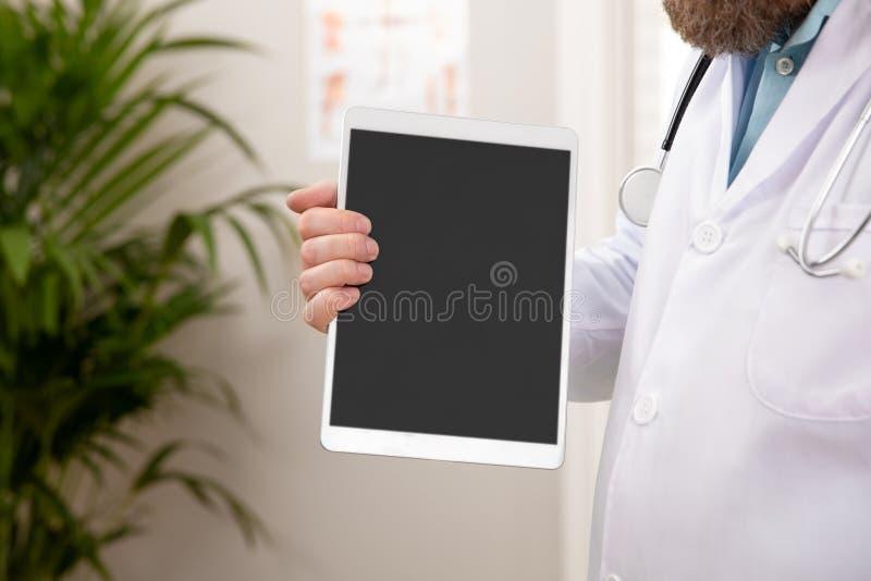 Doctor de sexo masculino adulto que muestra una imagen digital o un informe sobre una tableta foto de archivo