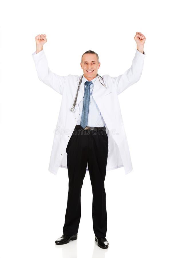 Doctor de sexo masculino alegre feliz con los brazos aumentados fotos de archivo