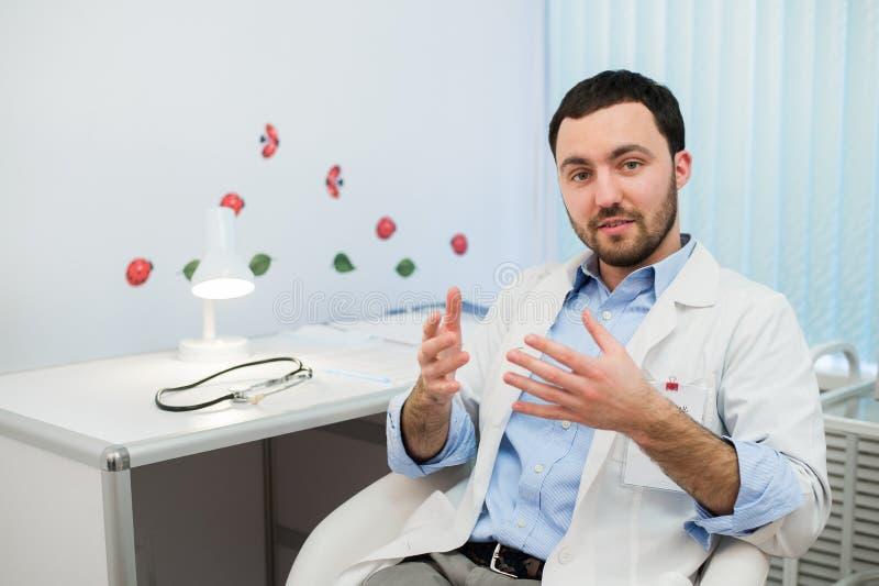 Doctor de sexo masculino amistoso del terapeuta de la medicina que se sienta en oficina, el hablar paciente y mirada a la cámara  imagen de archivo libre de regalías